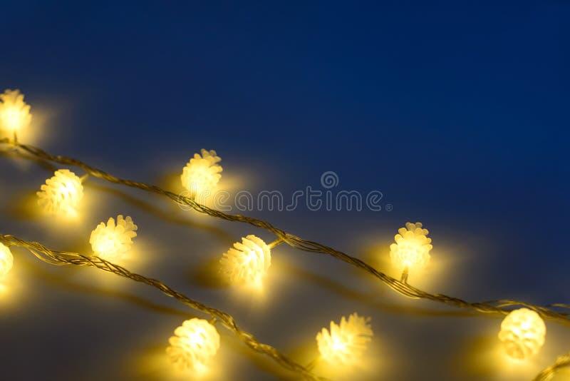 Luces de la Navidad amarillas borrosas en la forma de conos en tres filas en el fondo oscuro, profundidad del foco baja imagenes de archivo