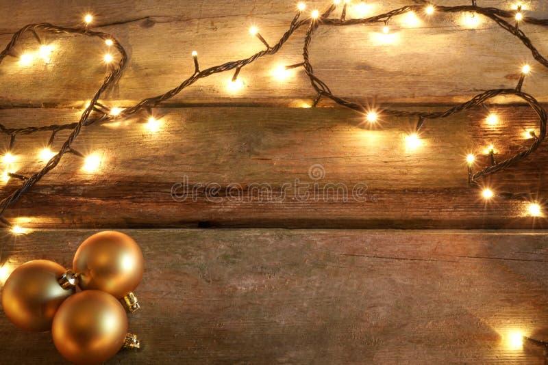 Luces de la Navidad amarillas en tabla de madera rústica con los ornamentos de oro de la Navidad en esquina Con el espacio de la  imagen de archivo