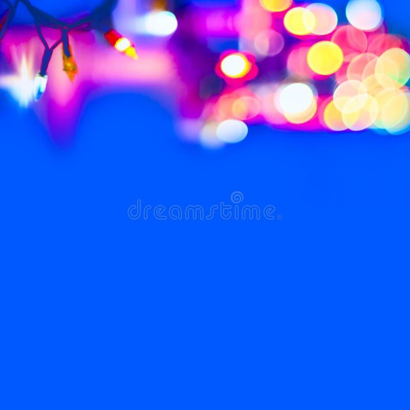 Luces de la Navidad borrosas coloridas decorativas en fondo azul Luces suaves abstractas Círculos brillantes coloridos de un Garl imagen de archivo