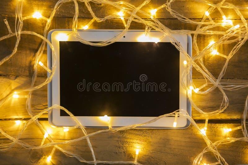 Luces de la Navidad sucias con la tableta digital foto de archivo