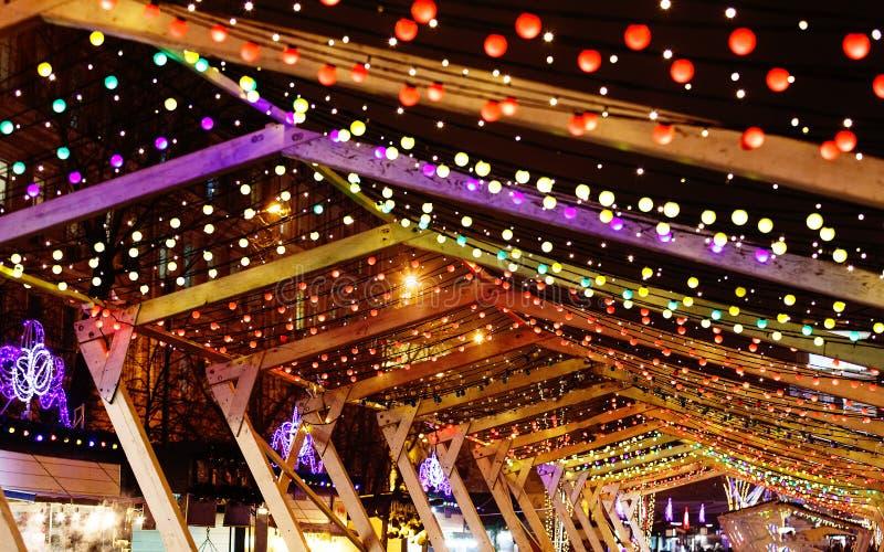 Luces de la Navidad y guirnaldas del bulbo en las calles de la ciudad Decoración del Año Nuevo y de la Navidad imagen de archivo