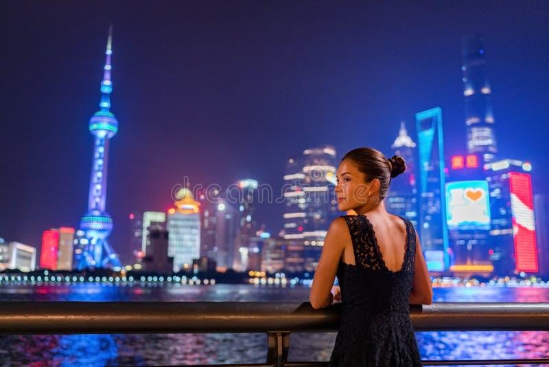 Luces de la noche de la ciudad de Shangai que brillan intensamente en cielo oscuro Señora elegante por el río de la Federación en fotografía de archivo libre de regalías