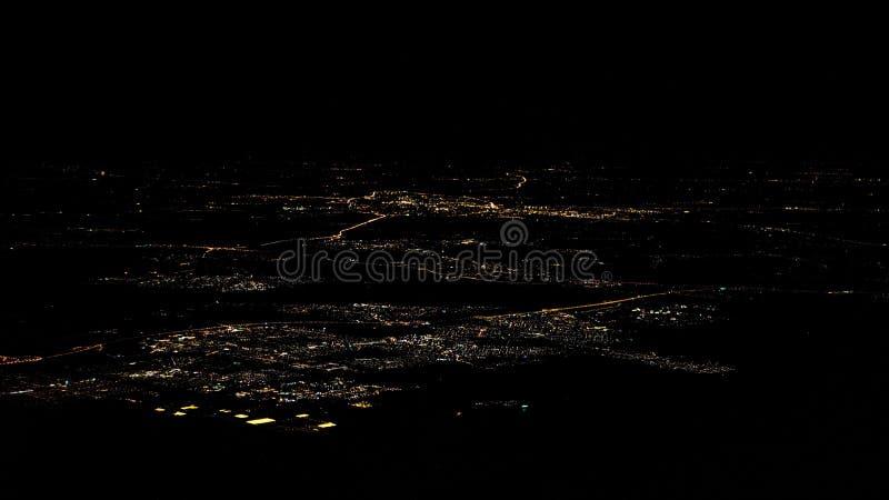 Luces de la opinión superior de la ciudad de Amsterdam de los caminos de la ventana del aeroplano en la noche foto de archivo libre de regalías