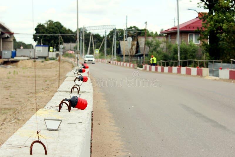 Luces de señal en los bloques fundamentales de concreto, cercando la construcción el viaducto del camino existente imagen de archivo libre de regalías