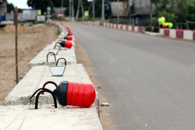 Luces de señal en los bloques fundamentales de concreto, cercando la construcción el viaducto del camino existente fotos de archivo