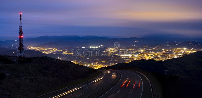 Luces del coche a la ciudad en la torre de la noche y de comunicaciones imagen de archivo libre de regalías
