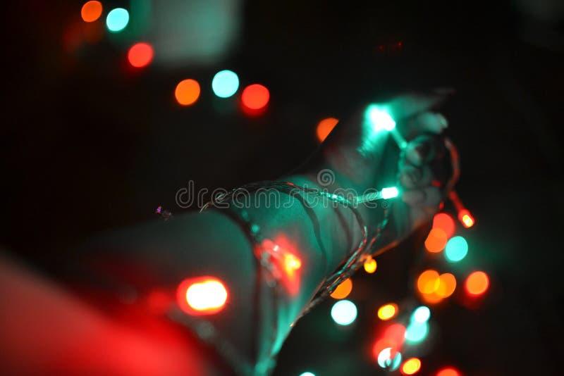 Luces en el bokeh colorido de la luz de la Navidad de la mano imagen de archivo