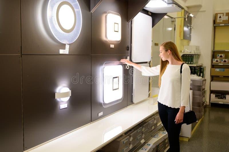 Luces hermosas de la lámpara de la mujer que hacen compras joven para su hogar foto de archivo libre de regalías