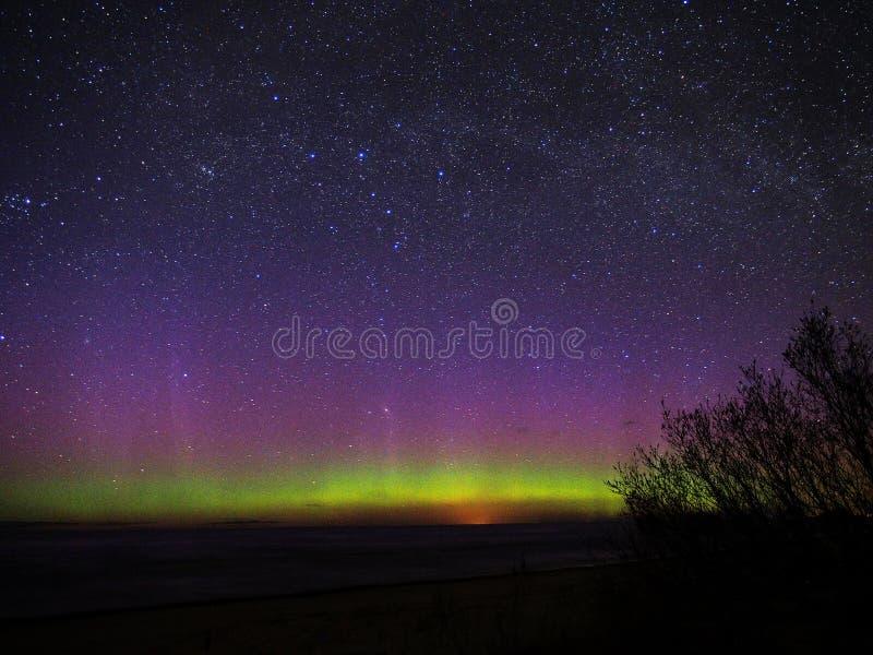 Luces polares y estrellas de la aurora sobre el mar fotos de archivo