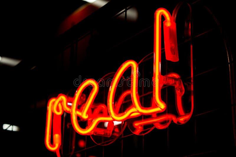 Luces REALES y borrosas de la muestra roja de neón que brilla intensamente en fondo negro foto de archivo