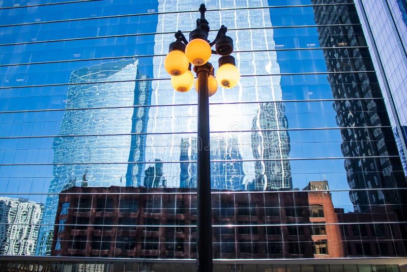 Luces relámpagos brillan frente a un reflexivo edificio de oficinas, que refleja las imágenes de los rascacielos circundantes fotos de archivo