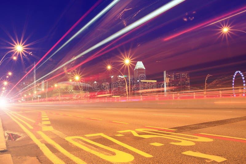 Luces rojas de la velocidad del autobús y de los coches en un camino a la ciudad imagen de archivo libre de regalías