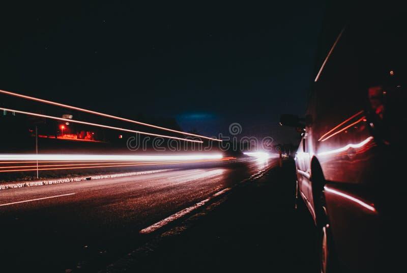 Luces rojas de un coche inminente rápido en una calle en el campo en una noche oscura azul del cielo con la luna hacia fuera foto de archivo libre de regalías