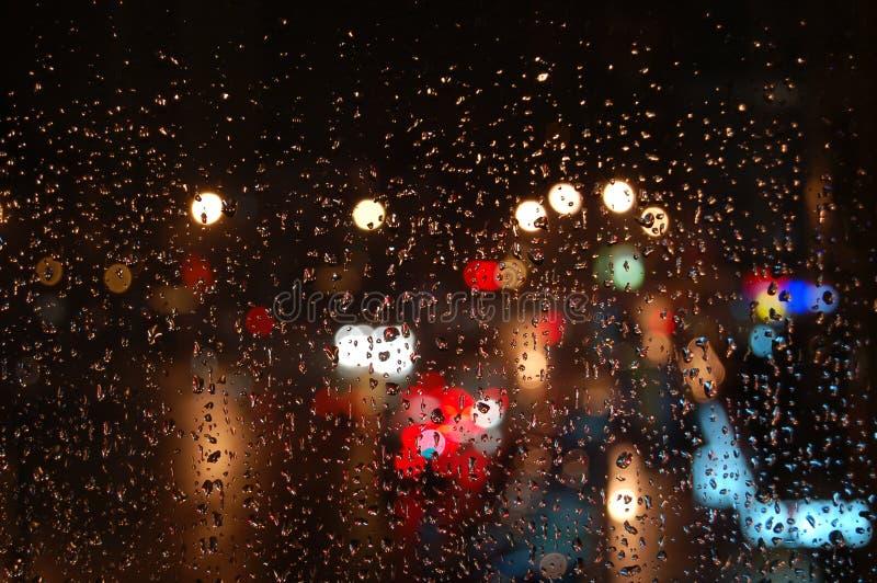 Luces a través de la ventana lluviosa foto de archivo