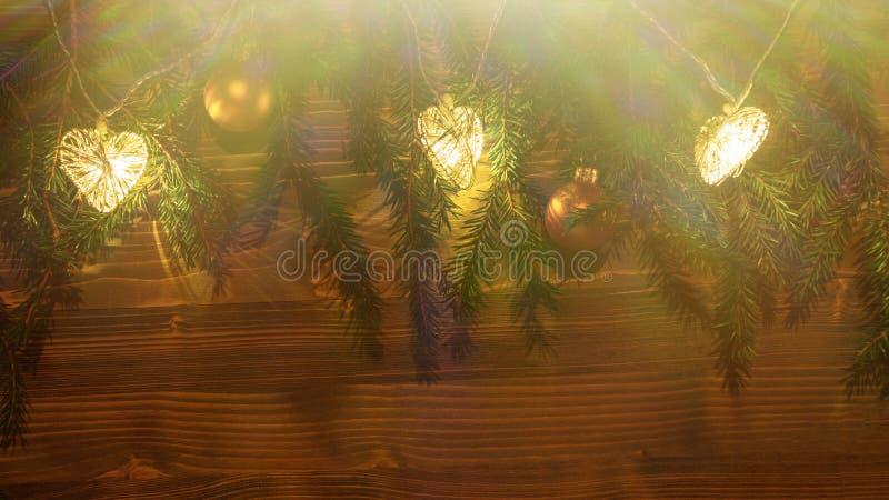 Luces y ornamentos de la Navidad en ramas de un árbol de navidad en un fondo de madera oscuro imagen de archivo
