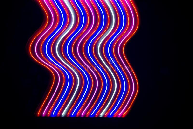 Luces y rayas que se mueven rápidamente sobre fondo oscuro imagen de archivo libre de regalías