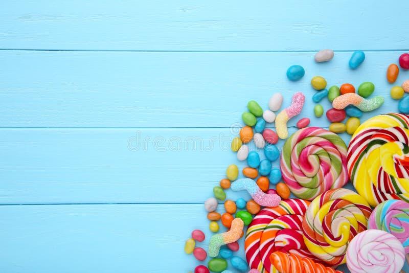 Lucettes colorées et sucrerie ronde colorée différente sur le fond bleu image stock