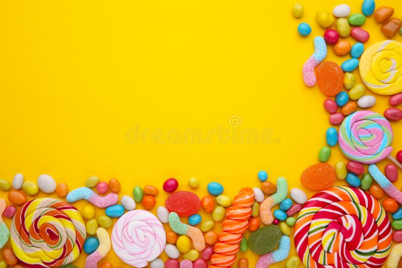 Lucettes colorées et sucrerie ronde colorée différente sur le fond jaune photos libres de droits