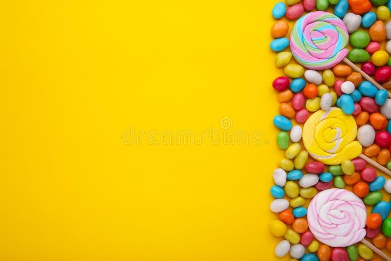 Lucettes colorées et sucrerie ronde colorée différente sur le fond jaune image libre de droits