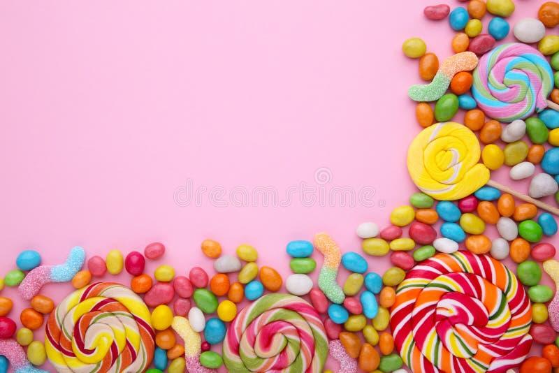 Lucettes colorées et sucrerie ronde colorée différente sur le fond rose image libre de droits