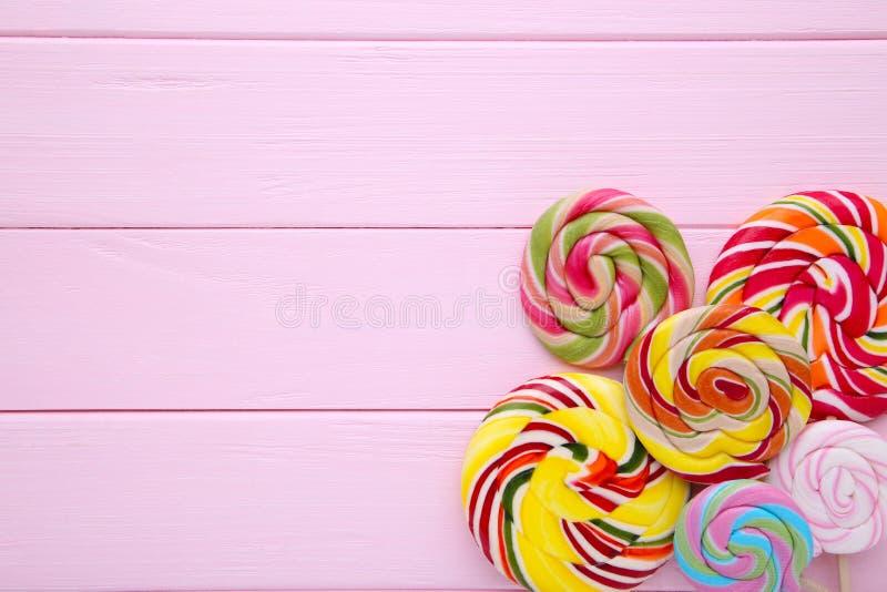 Lucettes colorées sur le fond en bois rose, bonbons photo libre de droits