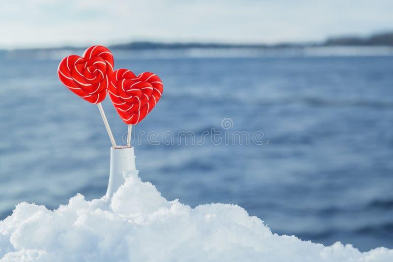 Lucettes de coeurs dans la neige sur le fond des vagues de mer Date romantique, déclaration de l'amour, Saint-Valentin image stock