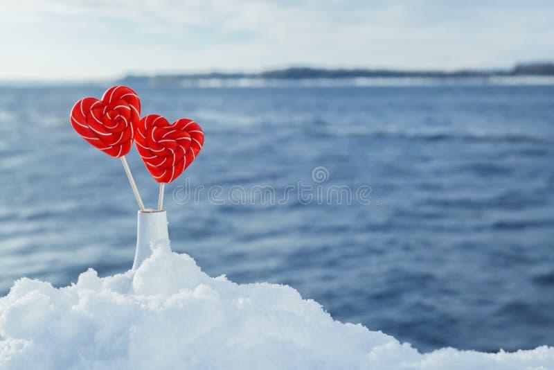 Lucettes de coeurs dans la neige sur le fond des vagues de mer Date romantique, déclaration de l'amour, Saint-Valentin photo libre de droits