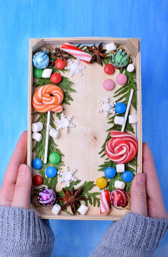 Lucettes de Noël, bonbons de différentes couleurs, guimauves et branches de thuja encadrant l'espace de copie photographie stock libre de droits