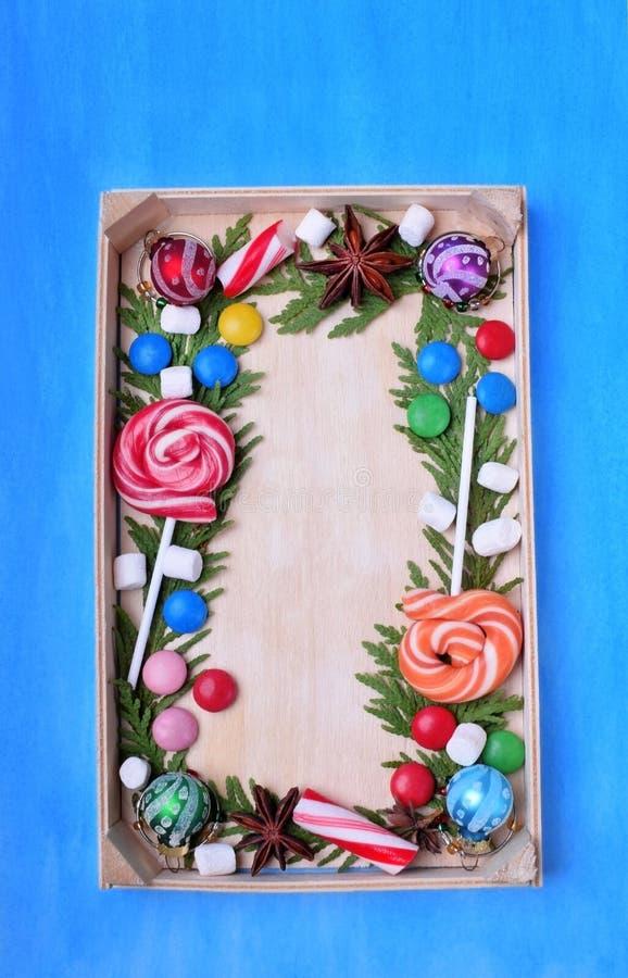 Lucettes de Noël, bonbons de différentes couleurs, guimauves et branches de thuja encadrant l'espace de copie sur un plateau en b photo stock