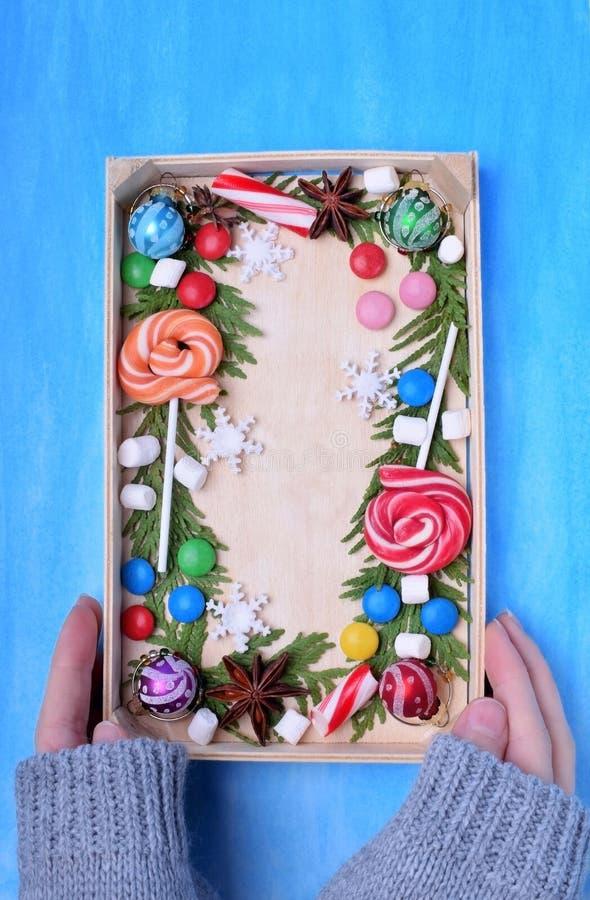 Lucettes de Noël, bonbons, guimauves et branches de thuja encadrant l'espace de copie sur un plateau en bois tenu par la femme photos stock