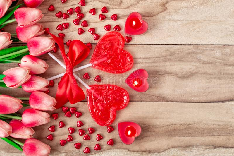 Lucettes en forme de coeur sur le fond en bois avec les bougies en forme de coeur garnies des fleurs de tulipes Fond de fête photos stock