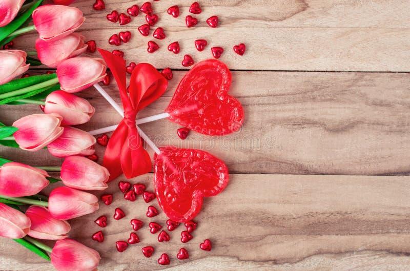 Lucettes en forme de coeur sur le fond en bois, garni des fleurs de tulipes Fond de fête à la Saint-Valentin image libre de droits