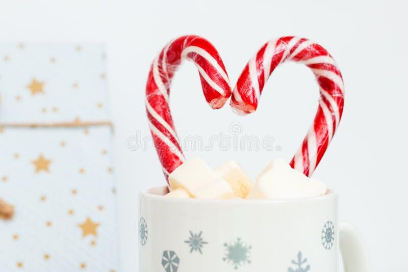 Lucettes en forme de coeur, tasse de cacao avec des guimauves et boîte-cadeau sur le fond blanc, carte de Noël flatlay simple photos libres de droits