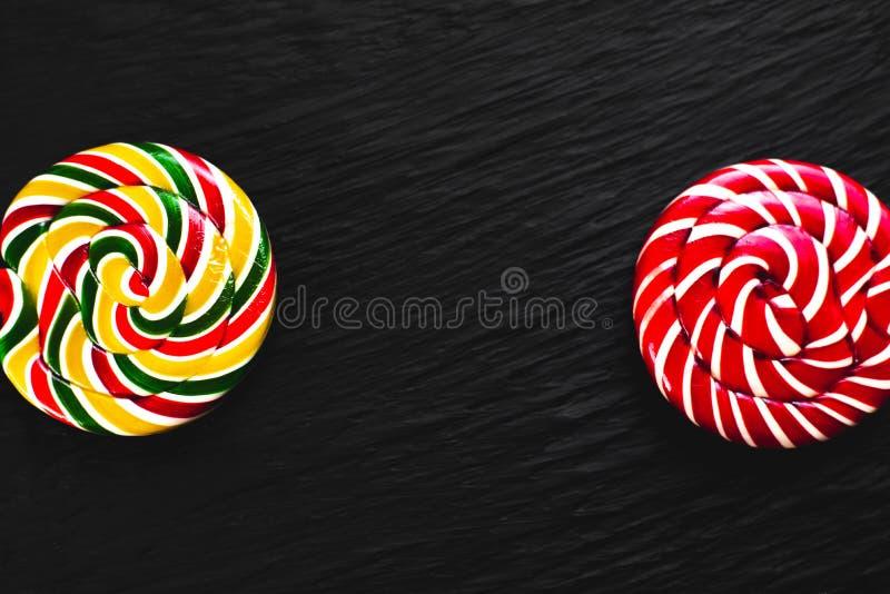 Lucettes rondes rouges et jaunes sur le fond noir avec la texture photographie stock