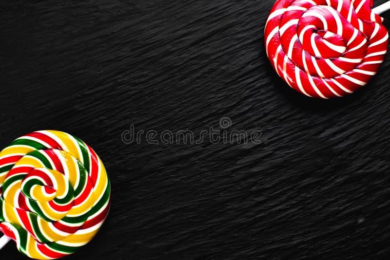 Lucettes rondes rouges et jaunes sur le fond noir avec la texture images stock