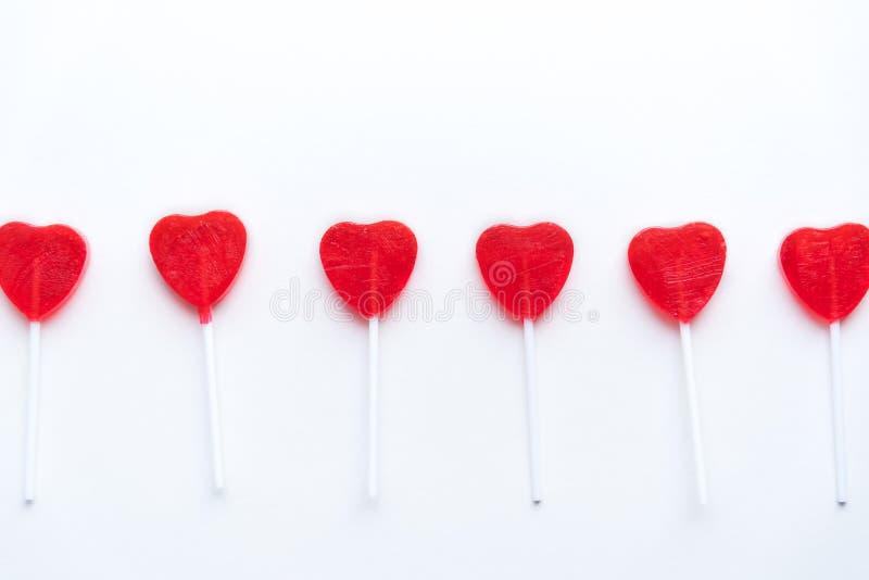 Lucettes rouges de coeur de Valentine dans une rangée à travers le fond blanc photos libres de droits