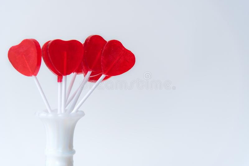 Lucettes rouges en forme de coeur de valentine dans le vase blanc avec le fond blanc photo libre de droits