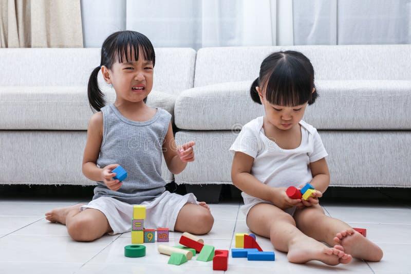 Lucha china asiática de las pequeñas hermanas para los bloques fotografía de archivo