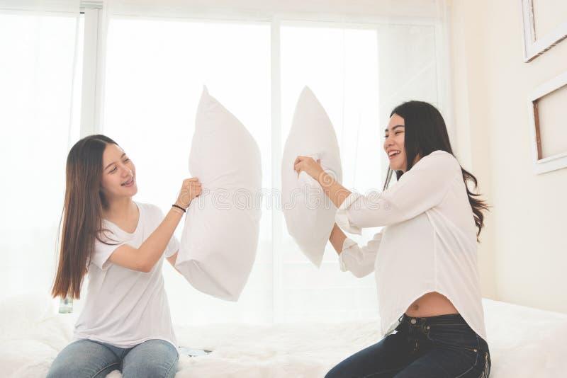 Lucha de almohada que hace asiática dos en dormitorio Concepto de las formas de vida y de la gente Tema de la relación y de la am imagen de archivo