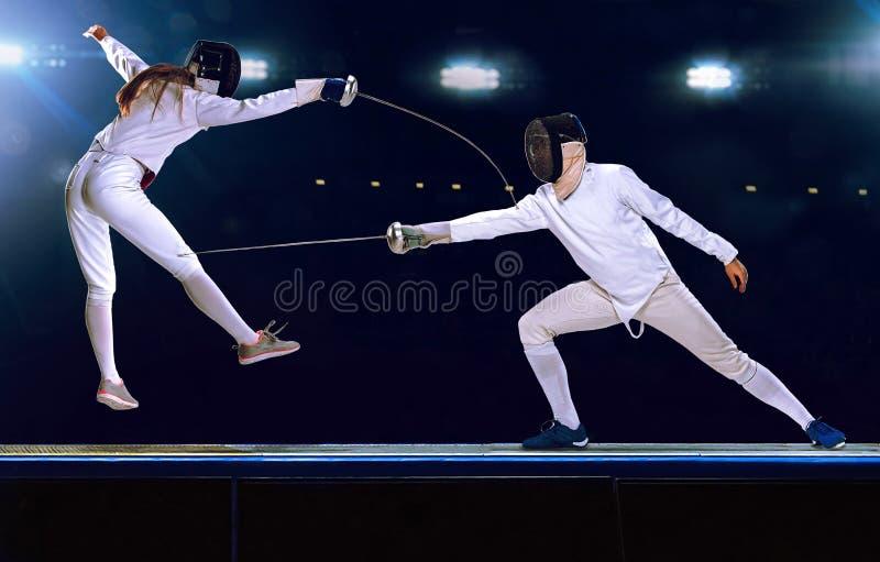 Lucha de cercado de dos atletas en la arena deportiva profesional fotos de archivo