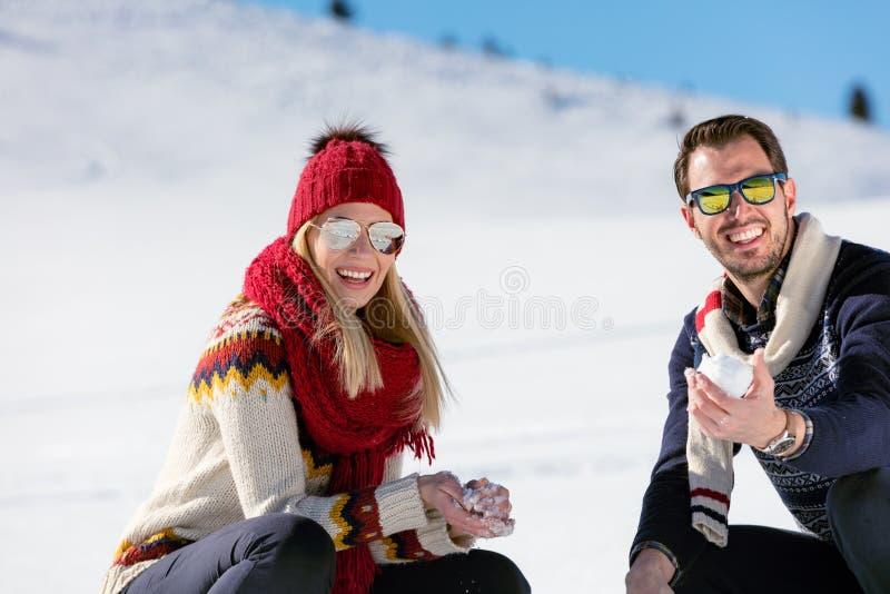 Lucha de la bola de nieve Pares del invierno que se divierten el jugar en nieve al aire libre Pares multirraciales felices alegre imagenes de archivo