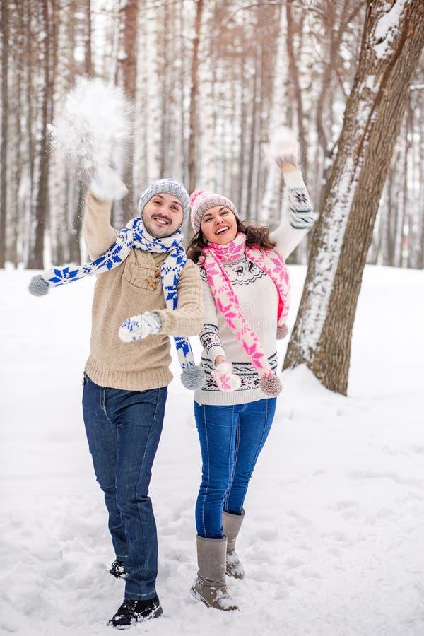 Lucha de la bola de nieve Pares del invierno que se divierten que juega en la nieve al aire libre foto de archivo