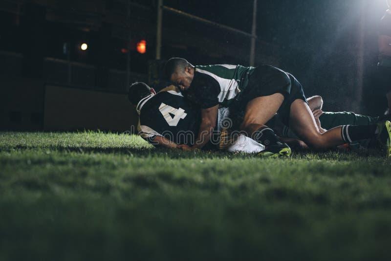 Lucha de los jugadores del rugbi para la bola foto de archivo