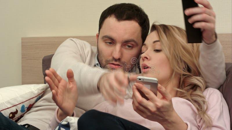 Lucha joven de los pares, discutiendo en cama en la noche porque mujer que manda un SMS alguien usando smartphone fotografía de archivo libre de regalías