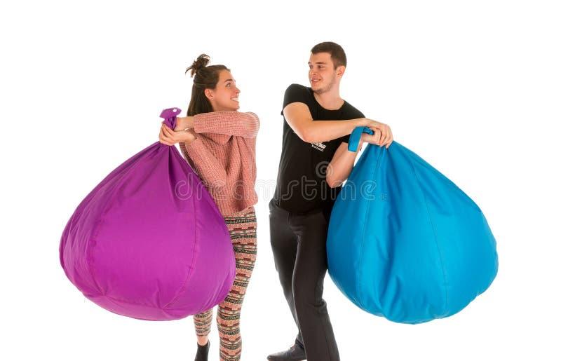 Lucha masculina y femenina joven con las sillas del beanbag fotografía de archivo libre de regalías
