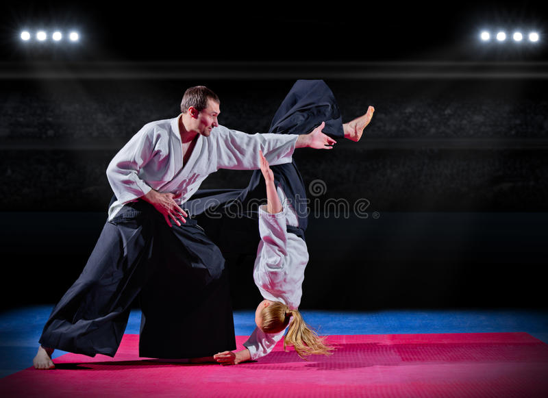 Luche entre los combatientes de los artes marciales en el pasillo de deportes imagen de archivo