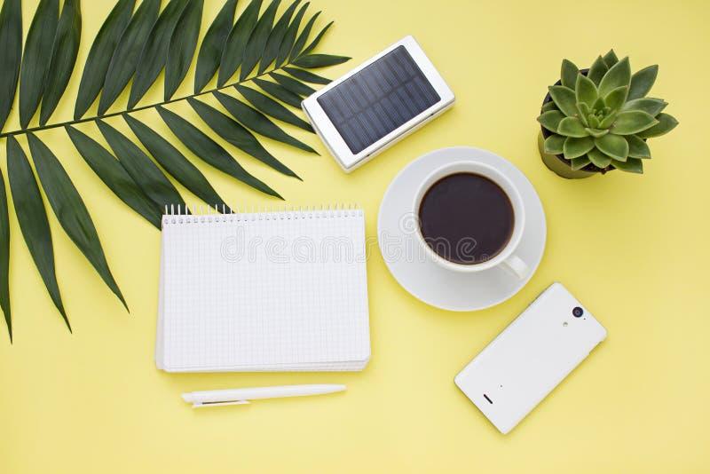 Lucht bedrijfskader met een zonnebatterij, een telefoon en een kop van koffie Hoogste mening royalty-vrije stock afbeelding