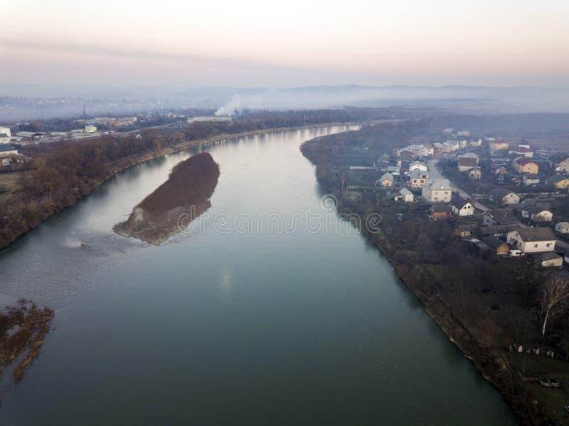 Lucht hoogste mening die van rivier door stad vloeien Landelijk landschap van woonhuisdaken, wegen en boombovenkanten op de lente royalty-vrije stock foto
