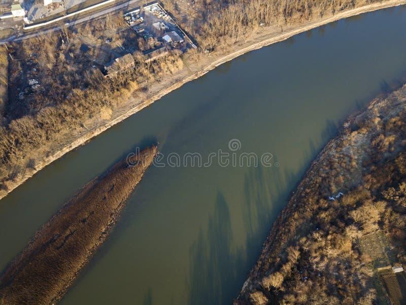 Lucht hoogste mening, plattelandspanorama van stil rivierwater en eiland met droog gras, nevelige horizon onder blauwe hemel op z stock afbeeldingen