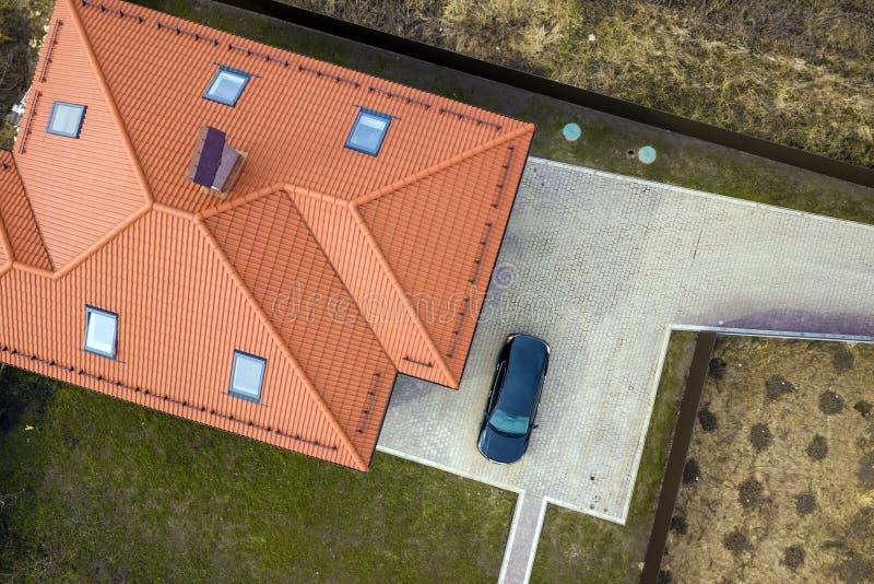 Lucht hoogste mening van de dakspaandak van het huismetaal met zoldervensters en zwarte auto op bedekte yard royalty-vrije stock foto's
